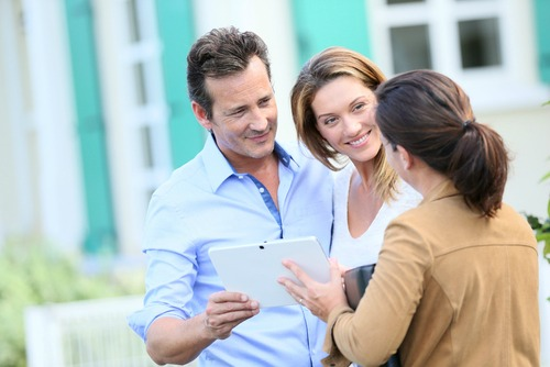 Couple looking at house with agent